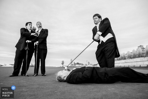 Black and white photo of men playing golf as one lays on the ground with the ball in his mouth and another pretends to put it by a Denver, CO wedding photographer.