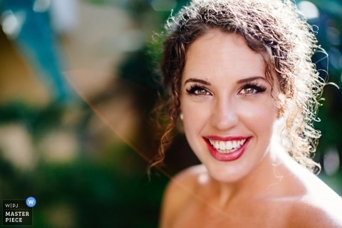 Portrait of the bride smiling and lit by natural sunlight by a Playa del Carmen wedding photographer.