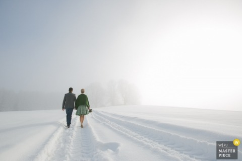 Photo of a man and woman walking hand-in-hand through the snow surrounded by a field of white.