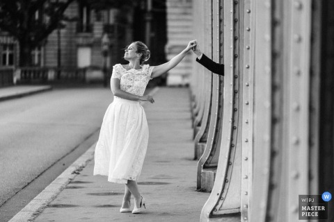 Black and white photo of the bride on a sidewalk as she holds the hand of her groom hidden behind a beam by a France wedding photographer.