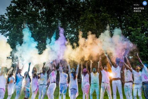 Retrato de invitados que lanzan tintes en polvo al aire por un fotógrafo de reportajes de bodas en Essex, Inglaterra.