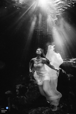 Black and white photo of the bride in her wedding gown underwater by a Costa Rica wedding photographer.