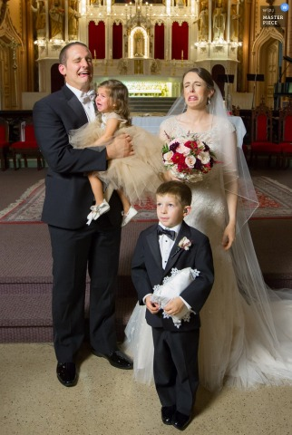 Portrait of the bride and groom making faces as they pose with two young children by a Chicago, IL wedding photographer.