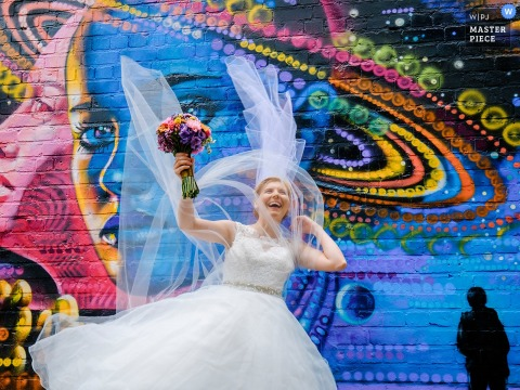 Photo of the bride smiling and holding up her bouquet in front of a colorful mural by a West Midlands, England wedding reportage photographer.