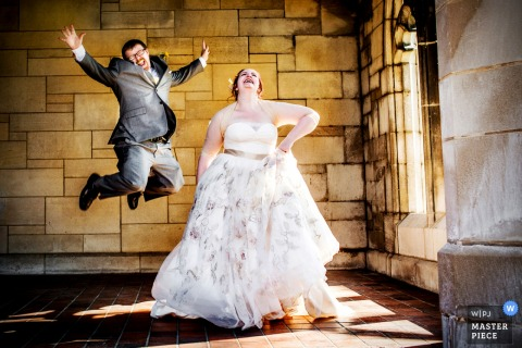 Portrait of the bride in her wedding gown as her groom leaps in the air behind her by a Chicago, IL wedding photographer.