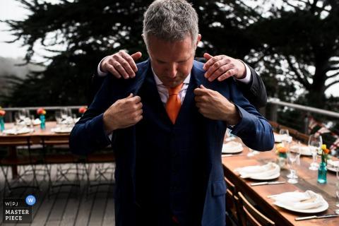 Een man helpt een ander met zijn pak op deze foto door een trouwreportfotograaf uit Londen, Engeland.