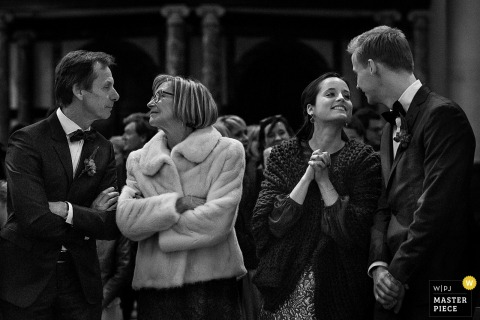 Black and white photo of an older couple and younger couple leaning toward each other by a Flanders wedding photographer.