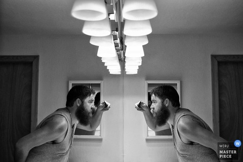 Black and white photo of a man looking at his reflection in the mirror as he gets ready by a Lake Tahoe, CA wedding photographer.