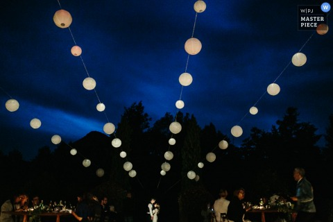 The bride and groom stand together in the distance surrounded by guests with lanterns above them in this photo by a Portofino wedding photographer.