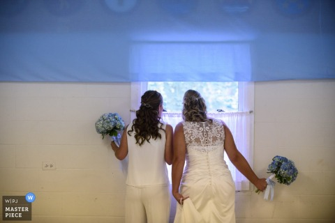 The bride looks out a window in this photo by an Omaha, NE wedding photographer.
