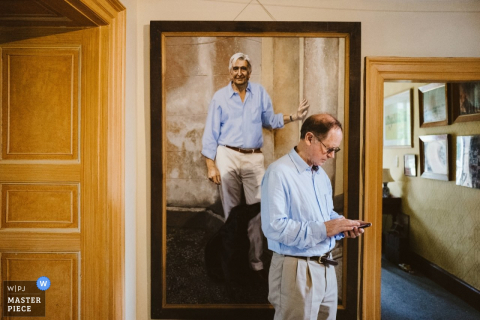 Photo of a man checking his phone in front of a painting of a man dressed identically to him by a Greater Manchester wedding reportage photographer.