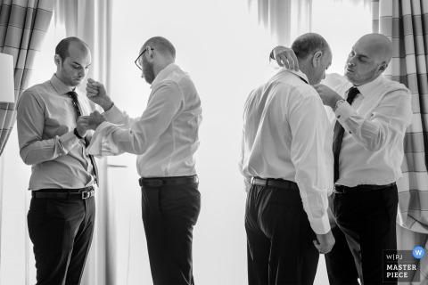 Zwart-witfoto van de bruidsjonkers die zich klaar maken voor de ceremonie door een trouwfotograaf uit Calabrië.