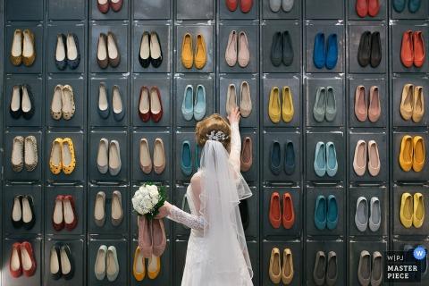 Eine Braut beobachtet eine Wand aus bunten Schuhen auf diesem Foto eines Hochzeitsfotografen aus Rom.