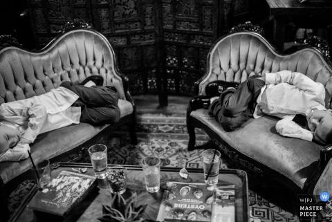 Foto en blanco y negro de dos jóvenes invitados descansando en asientos de amor de un fotógrafo de bodas de San Antonio, Texas.