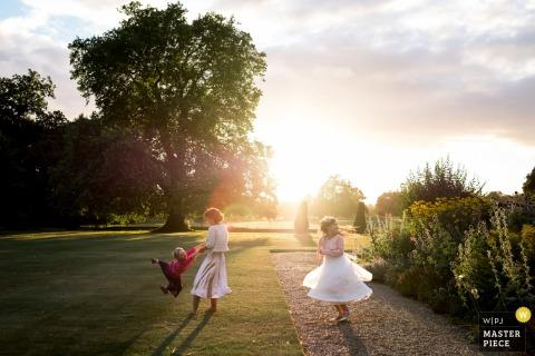 Drie jonge kinderen spelen in de zonovergoten tuin in deze foto door een fotograaf van de het huwelijksreportage van Londen, Engeland.