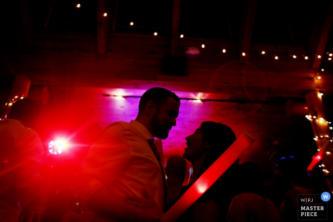 Photo of the guests on the dance floor with bright red lights by a Tunbridge, VT wedding photographer.