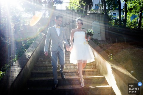 The bride and groom walk down a flight of stairs outside as the sun's rays shine over them in this photo by a Lombardy wedding photographer.