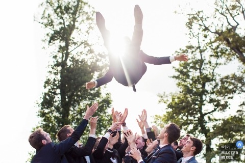 The groomsmen throw the groom in the air outside as the sun beams through the trees in this photo by a France wedding photographer.