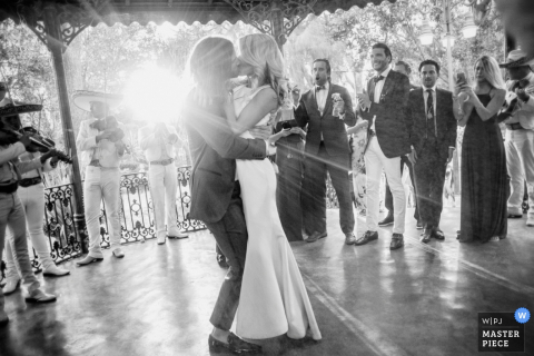The bride and groom kiss in a gazebo as musicians play and the sun shines through in this black and white photo by a San Diego, CA wedding photographer.