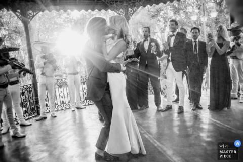 Los novios se besan en un mirador mientras los músicos tocan y el sol brilla en esta foto en blanco y negro de un fotógrafo de bodas de San Diego, California.