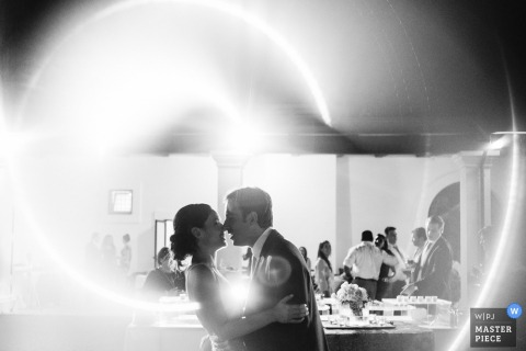 The bride and groom hold each other as a light spirals around them in this black and white photo by a Taranto, Italy wedding photographer.
