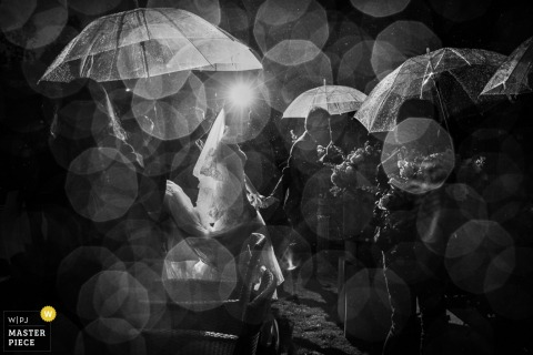 Das Licht wird vom Regen gebrochen, während sich die Gäste in diesem Schwarzweißfoto eines chinesischen Hochzeitsfotografen mit klaren Sonnenschirmen schützen.