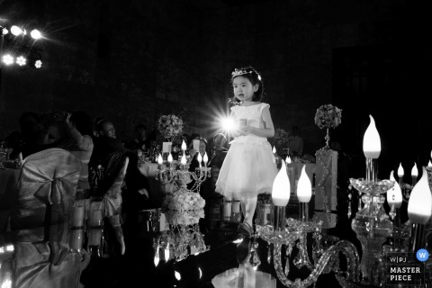 A small girl in a white dress stands on a bar while guests celebrate around her in this black and white photo by a Beijing, China wedding photographer.