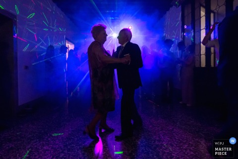 An older couple dances on the dance floor in blue light in this photo by a Venice wedding photographer.