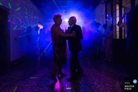 Een ouder paar danst op de dansvloer in blauw licht in deze foto door een het huwelijksfotograaf van Venetië.