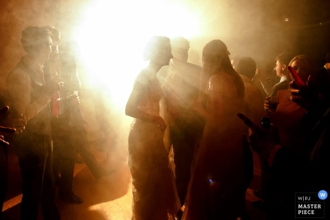 A photo of the bride and her guests obscured by light by a Paris wedding photographer.