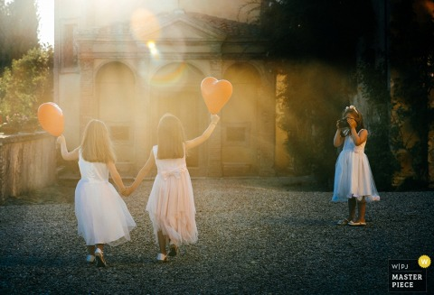 A girl takes a photo of two young girls in white dresses holding red heart balloons in the sunlight in this photo by a Rome wedding photographer.