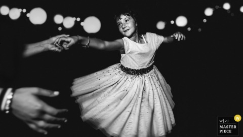 A young girl is twirled on the dance floor surrounded by lights in this black and white photo by a France wedding photographer.