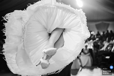 Black and white detail photo of the bride's heels and dress in the air on the dance floor by a Zurich, Switzerland wedding photographer.