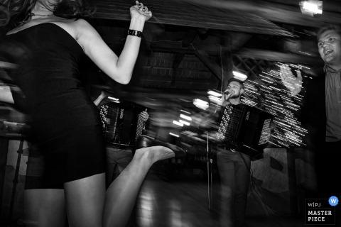Una invitada levanta los talones en la pista de baile mientras un hombre toca el acordeón en esta foto en blanco y negro de un fotógrafo de bodas de Praga.