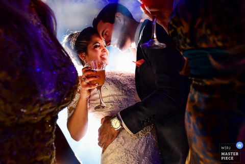 Photo of the groom holding his bride taken between other guests by a Brazil wedding photographer.