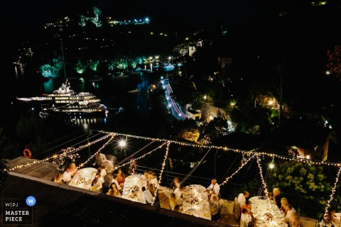 Photo of the outdoor, nighttime reception from above as guests dine at their tables by a Portofino wedding photographer.