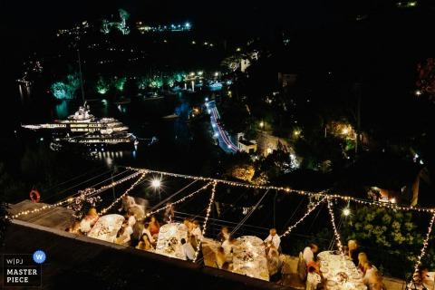 Foto des nächtlichen Empfangs im Freien von oben, während die Gäste von einem Portofino-Hochzeitsfotografen an ihren Tischen speisen.