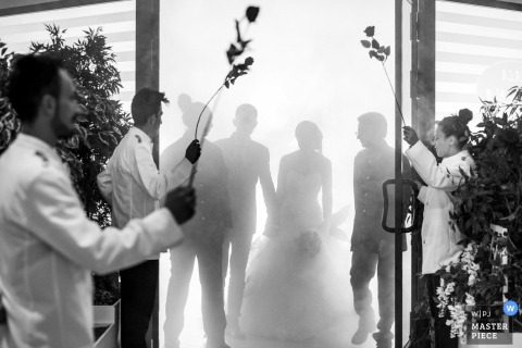 The bride and groom are silhouetted as they prepare to enter the reception hall in this black and white photo by a Calabria wedding photographer.