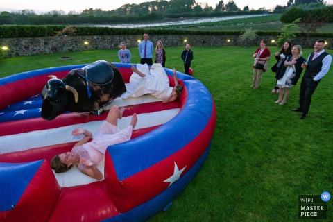 Photo of the bride and a guest after they were bucked off by a mechanical bull by a Devon, England wedding reportage photographer.