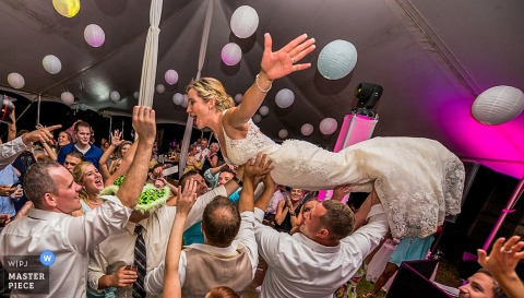 La foule de la mariée surfe sur ses invités sur cette photo prise par un photographe de mariage de Charlotte, Caroline du Nord.