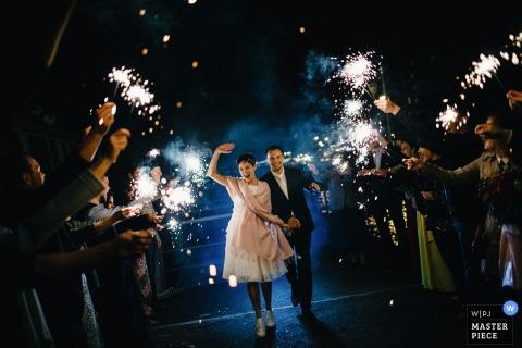 Bruiloftsgasten staan in twee rijen met sterretjes terwijl de bruid en bruidegom tussen hen in wandelen op deze foto door een Russische huwelijksfotograaf.