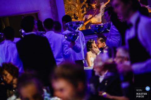 Een Russische huwelijksfotograaf vangt de bruid en bruidegom die door de menigte kussen op deze ontvangstfoto.
