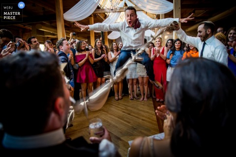 Photo of guests celebrating during the reception as one man leaps in the air by a Chicago, IL wedding photographer.