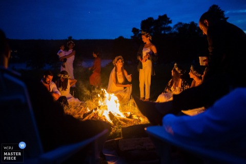 The bride and guests enjoy an evening by the fire in this photo by a Maine wedding photographer.