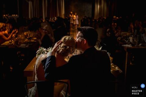 Pan młody ściąga swoją pannę młodą na pocałunek w głowę na tym zdjęciu przez fotografa ślubnego z Chicago, IL.