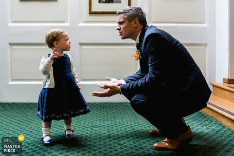 A man bends down to talk to a little girl in this photo by a Bristol, England wedding photographer.