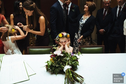A young girl stares at a bouquet of flowers while the other guests mingle in this photo by a London, England wedding reportage photographer.
