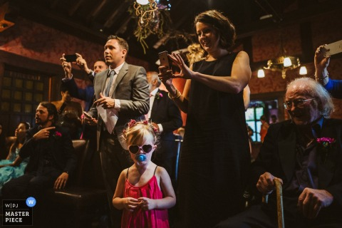 Guests take photos of the ceremony as a small girl in a pink dress and sunglasses stares directly at the camera in this photo by a Greater Manchester wedding reportage photographer.