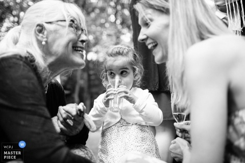 Black and white photo of a young girl sipping her drink from a glass while watching the two women in front of her as they laugh by a Lower Saxony, Germany wedding photographer.