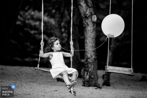 Black and white photo of a young girl on a swing holding a balloon in her mouth by its string by a Luxembourg wedding photographer.